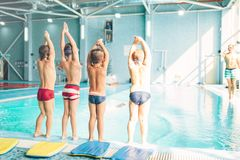 Boys doing sportive exercises with hands up. Near pool, view from back. Sporty kids preparing for swim. Kids doing exercise near sweeming pool. Healthy and Royalty Free Stock Photo