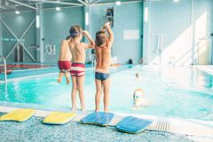 Boys doing sportive exercises with hands up. Near pool, view from back. Sporty kids preparing for swim. Kids doing exercise near sweeming pool. Healthy and Stock Images