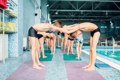 Boys doing sportive exercises in pairs near pool. Sporty kids preparing for swim. Kids doing exercise near sweeming pool. Healthy and happiness childhood Stock Image