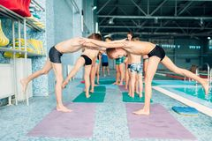 Boys doing sportive exercises in pairs near pool. Sporty kids preparing for swim. Kids doing exercise near sweeming pool. Healthy and happiness childhood Royalty Free Stock Image