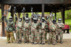 Boys dressed in camouflage stand on paintball base Royalty Free Stock Image