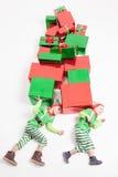Boys dressed Elf costumes holding many gift boxes. Black Friday. Stock Photos