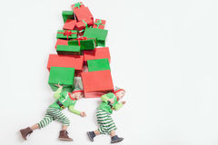 Boys dressed Elf costumes holding many gift boxes. Black Friday. Stock Photos