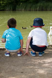 Boys at duck pond. Two little boys watch and feed the ducks at a park Stock Photos