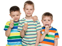 Boys eat ice cream. Three fashion boys are standing together and eat ice cream Stock Image