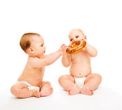 Boys eating bread roll. Two boys in diapers eating bread roll Royalty Free Stock Images