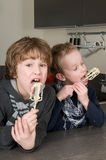 Boys Eating Dough From A Beater Stock Photography