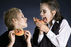 Boys eating Halloween cookies. Is really his cookie better than mine? Two boys dressed up as vampires with Halloween biscuits Stock Photo