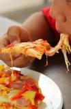 The boys eating Italian pizza ham cheese Stock Image