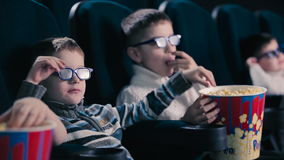 The boys are eating the popcorn in the cinema. The boys are watching the movie and laughing stock footage