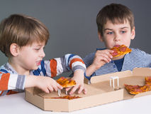 Boys enjoy eating pizza Stock Image