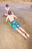 Boys enjoy surfing with a boogie board Stock Image
