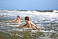 Boys enjoy the waves in the ocean Stock Photo