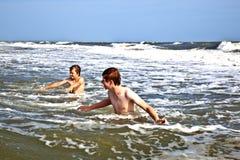 Boys enjoy the waves in the ocean Stock Photo