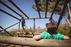 Boys exercising on monkey bar during obstacle course. In boot camp Stock Image