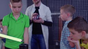 Boys explores Tesla coil and lamp in museum of popular science and technologies. Children and laboratory assistant make physical experiment with Tesla coil in stock video footage