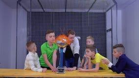 Boys explores van de graaff generator in scientific museum. Children and laboratory assistant make physical experiment with Van de Graaff generator in scinetific stock video footage