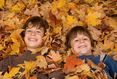 Boys in the Fall Leaves. Boys Smiling Playing in the Fall Leaves Royalty Free Stock Photography