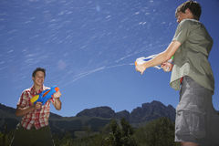 Boys Fighting With Water Guns In Mountains Royalty Free Stock Image