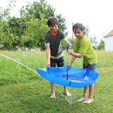 Boys filling umbrella with water Stock Photography
