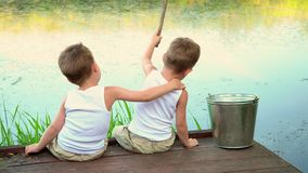 Boys fish in white undershirts. Beautiful children have a good time in the summer on the lake. On this video you can see as two little brothers sit on a pier at stock video