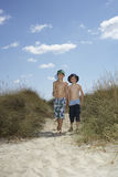 Boys With Fishing Net Walking On Sand Dunes. Full length portrait of two boys walking on sand dunes with fishing net stock photo