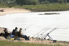 Boys fishing in the river Waal stock images