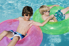 Boys On Float Tubes In Swimming Pool Stock Photo