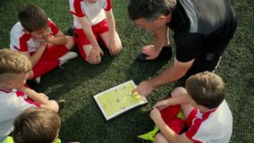 Boys football players are listening trainer and looking on scheme of play. Team of little boys football players is listening trainer and looking on scheme of stock video