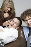 Boys & girl / cellphone. Girl beside a leather couch is leaning down holding a cell phone to the ear of a boy lying down on the couch. (Boys in relaxed office Royalty Free Stock Photo