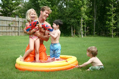 Boys and girl play with dad in stock photo