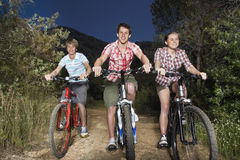 Boys And Girl Riding Bicycles On Country Road Stock Images