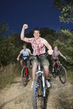 Boys And Girl Riding Bicycles On Country Road Royalty Free Stock Image