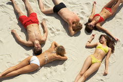 Boys and girls. Above view of young slip teens sunbathing at beach Royalty Free Stock Image
