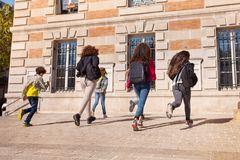 Boys and girls with backpacks running to college Stock Image