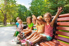 Boys and girls on the bench in park Royalty Free Stock Photo