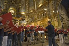Boys & girls choir singing in the Benedictine Abbey at Montserrat, Santa Maria de Montserrat, near Barcelona, Catalonia, Spain wit. H Black Madonna in background Royalty Free Stock Image