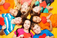 Boys and girls in circle with hearts. Boys and girls laying on the floor in circle with hearts in their hands Stock Images