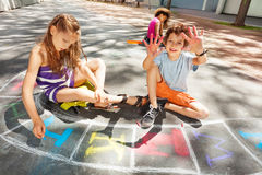 Boys and girls draw chalk on the road. Kids draw with chalk on the road and happy handsome boy shows hands to the camera Stock Images
