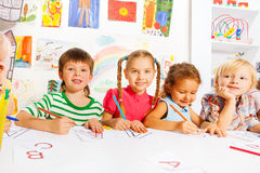 Boys and girls drawing letters in writing lesson Stock Image