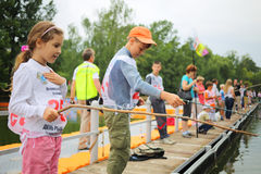 Boys and girls fishing at Fishermans Day. MOSCOW - JUL 14: Boys and girls fishing at Fishermans Day in the Exhibition Center on July 14, 2013 in Moscow, Russia stock photography