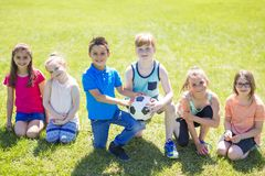 Boys and girls football portrait. Boys and girls running towards ball on a field Stock Images