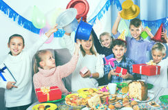 Boys and girls handing gifts to each other during dinner Stock Images