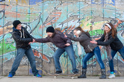 Boys and girls having fun on the street. Happy teenage boys and girls having fun in urban environment royalty free stock photos