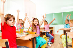Boys and girls hold hands up sitting in class Royalty Free Stock Image