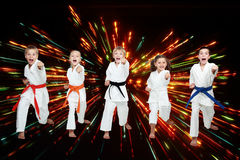Boys and girls in kimono are beating blows arms on black background with colored flares Stock Photos
