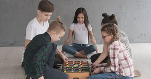 Boys and girls playing foosball at home. Little boys and girls playing foosball sitting on floor at home stock footage