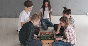 Boys and girls playing foosball. Little boys and girls playing foosball while sitting on floor at home stock footage