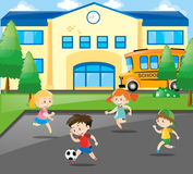 Boys and girls playing football at school Stock Photo