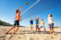 Boys and girls playing volleyball on the beach. Big group of teenage boys and girls playing volleyball on the beach stock images